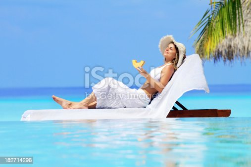 476618818 istock photo Lady relaxing in the chaise lounge on a exotic resort. 182714296
