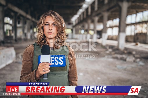 One woman, war journalist with microphone at the place of action, in war zone.