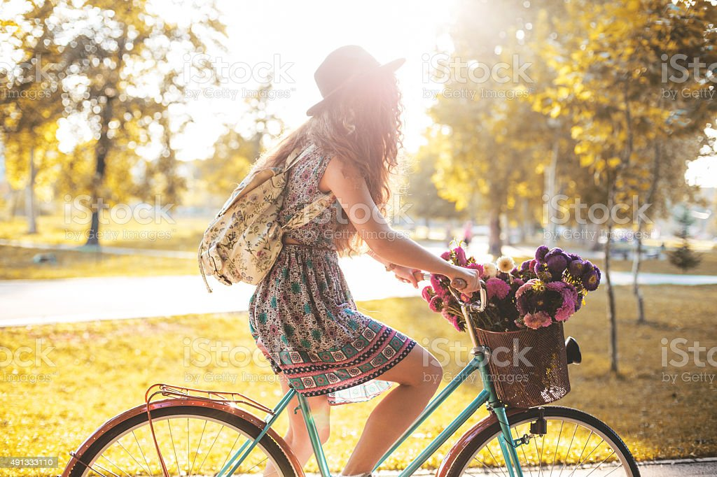 Lady riding her hipster retro bike in vintage style stock photo