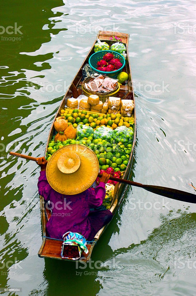 Lady selling fruit from her boat at Floating Market, Thailand stock photo