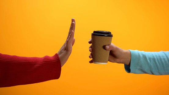 Lady showing stop gesture to paper cup on bright background, recycling problem