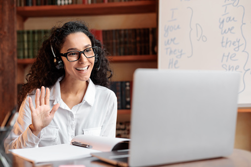 Distance Education. Positive lady wearing glasses and wireless headest at virtual meeting, sitting at desk, having video call on laptop, waving to webcam. Woman studying or teaching online at home