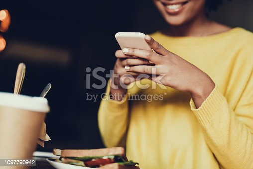 616898108istockphoto Lady sitting inside cafe and looking at telephone 1097790942