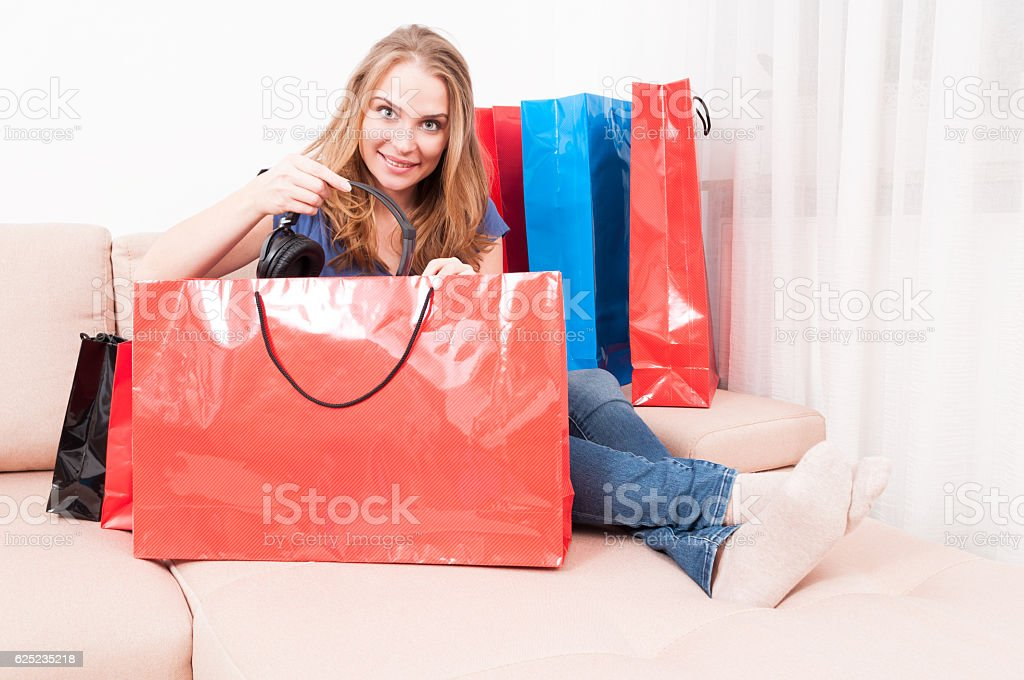 Lady sitting on couch finding headphones in shopping bags stock photo