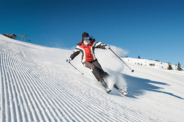 Lady skiing downslope on modified piste stock photo