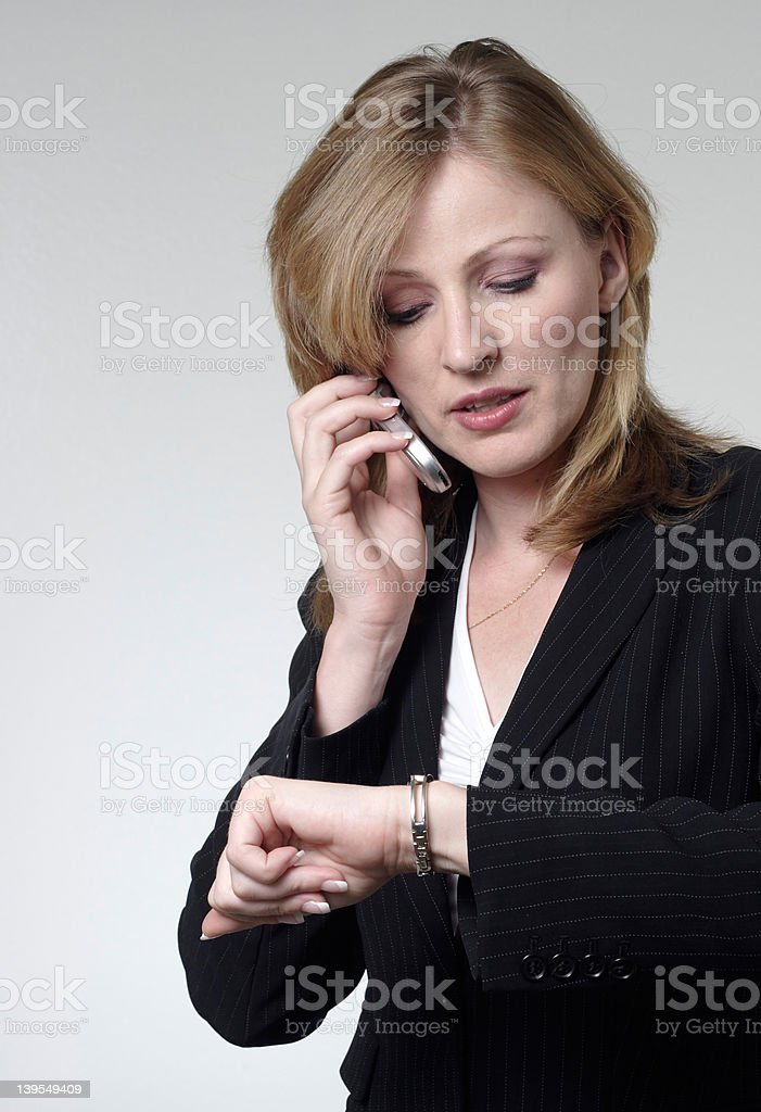 lady talking on cell phone checking her watch royalty-free stock photo