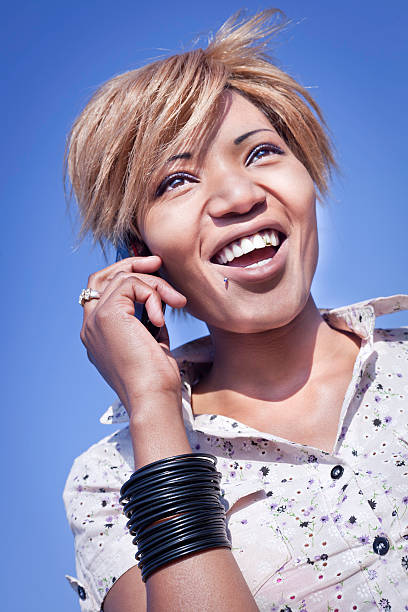 lady talking on her mobile smiling - gold tooth stock photos and pictures