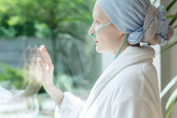Lady touching glass Young lady with tumor touching the hospital window glass oxygen tube stock pictures, royalty-free photos & images