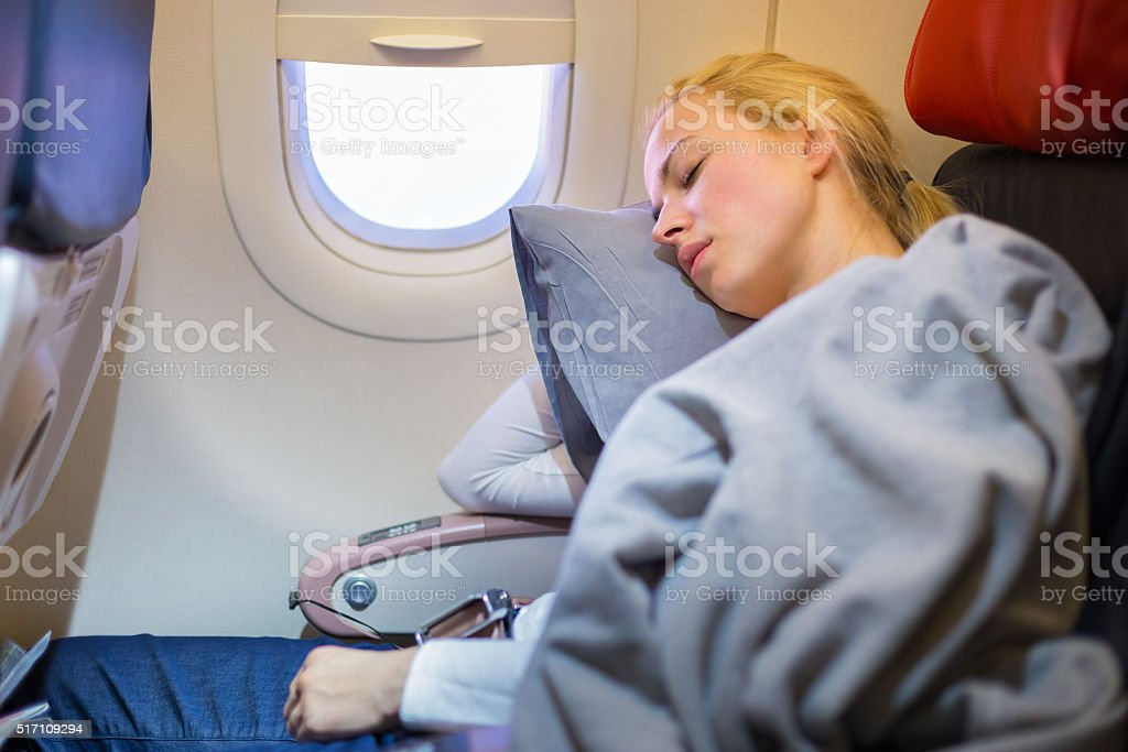 Lady traveling napping on a plain. stock photo
