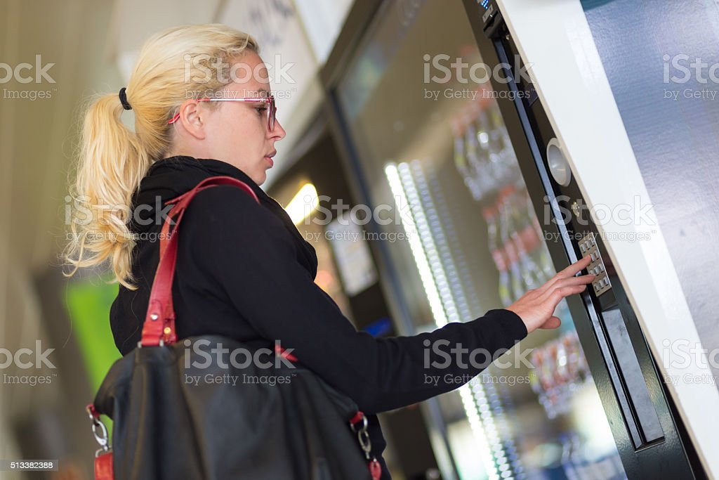 Lady using  a modern vending machine stock photo