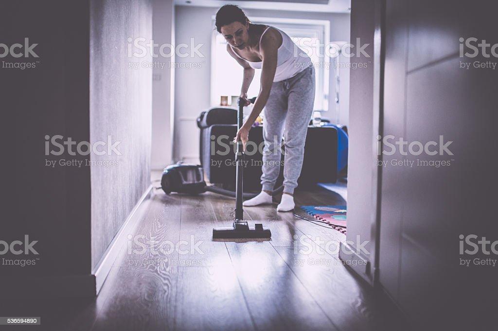 Lady vacuuming the laminate stock photo