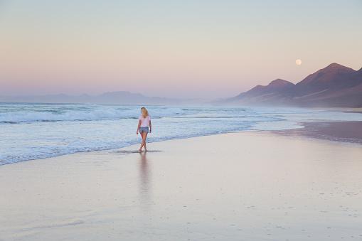 Lady walking on sandy beach in sunset.