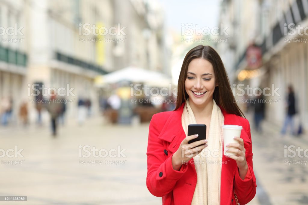 Front view portrait of a happy lady walking in the street using a...