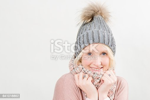Blonde lady smiling and wearing a scarf and a pom winter hat, posing as if chilling in the cold over a white background with copy space