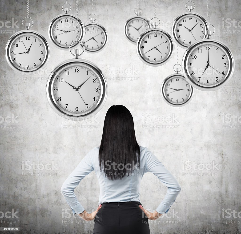 lady who is looking at hovering pocket watches in air stock photo