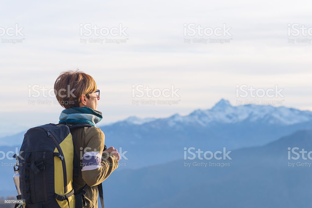Lady with backpack looking at majestic panorama on the Alps stock photo