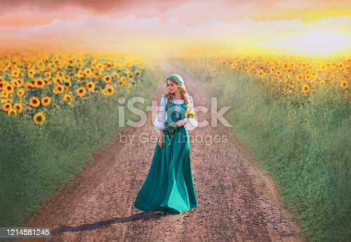 charming girl in green long dress with white shirt walks along road, lady with blond braids holds yellow flowers in hands, rural beauty returns home from field, art photo with pink sky at sunset.