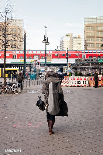 Berlin, Germany - December 8, 2017: Lady with guitar in the street in the city center of Berlin in Germany in Europe in winter. Train on the bridge on Alexanderplatz.