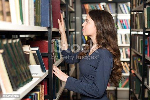istock lady with loose long dark hair choosing a book 499284736
