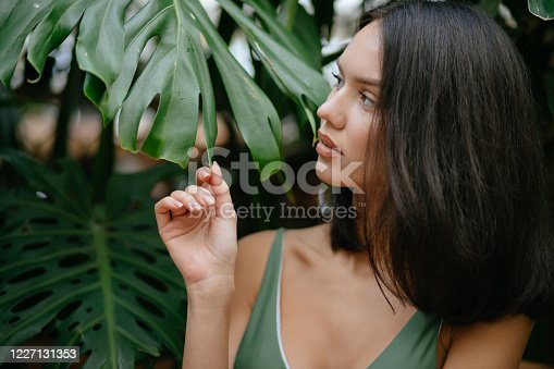 attractive lady with natural beauty posing in rainforest, sensual woman feels free in forest, close to wildlife. romantic gorgeous brunette woman in green swimsuit