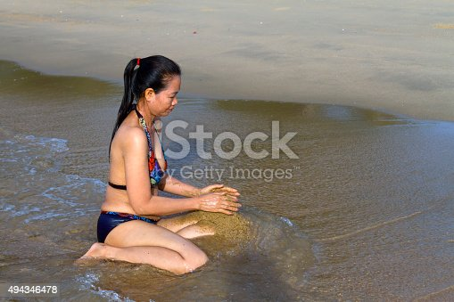 494377786istockphoto Lady with swimsuit play sand 494346478
