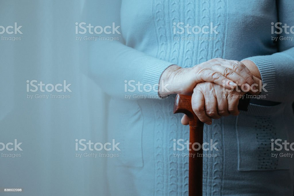 Lady with walking stick stock photo