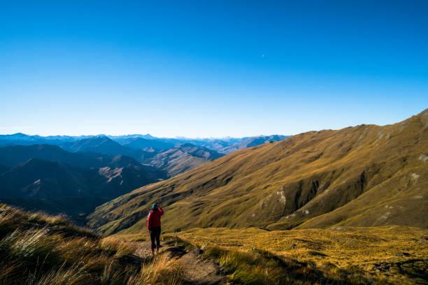 Eine Dame mit warmen Anzug, eine schöne Landschaft eine gelbe Grünland blauen Himmel und Alpen Berge bei Sonnenuntergang zu genießen. – Foto