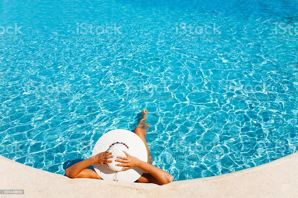 Mujer con sombrero blanco de colocación en el blue water - foto de stock