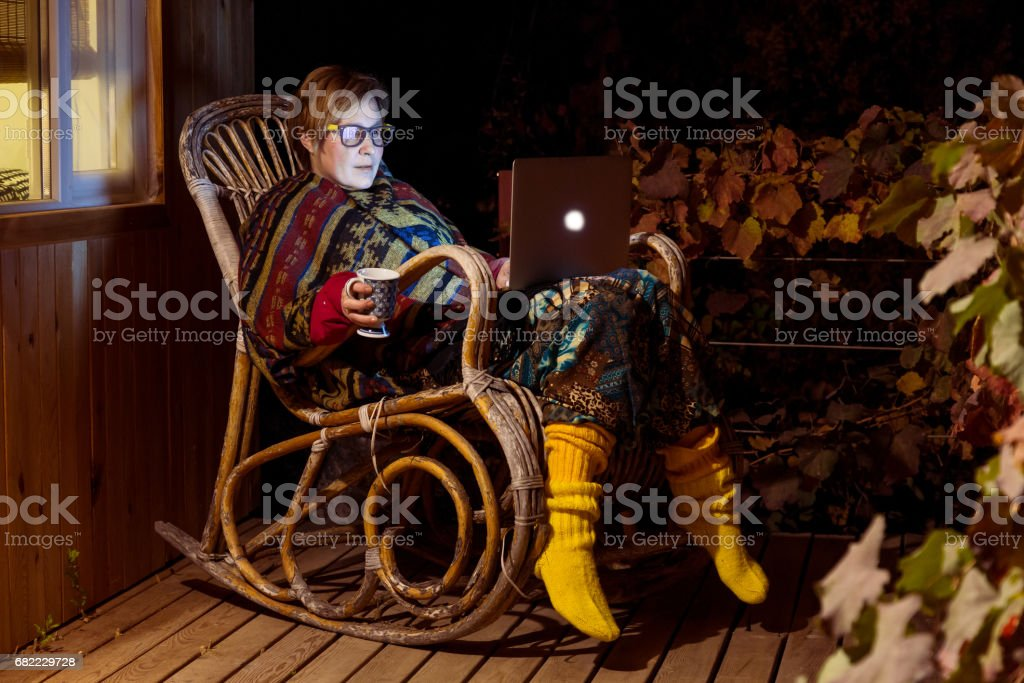 Lady working on Computer at rocking Chair stock photo