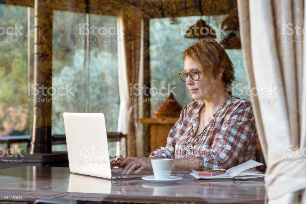 Lady working on Freelance Project in Cafe throw Window View stock photo