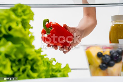 Healthy care and diet concept. Close up portrait of young womans hand choosing sweet pepper from shelf in opened refrigerator with fruits and vegetables