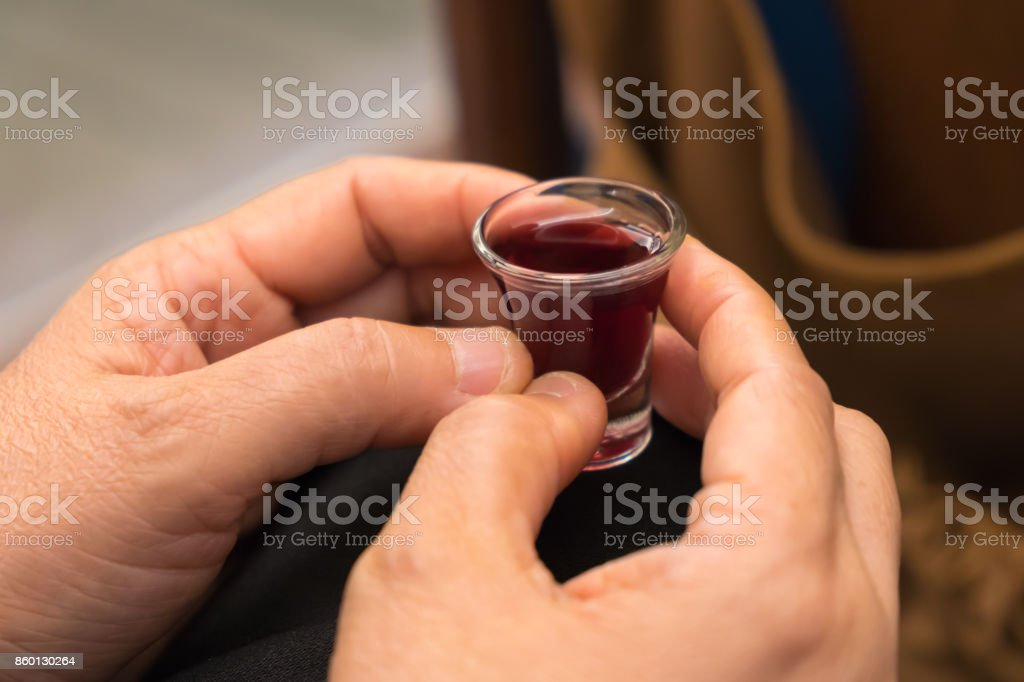 A lady's hands hold a red wine cup in Holy Communion. stock photo