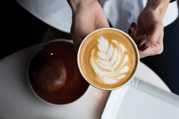 Lady's hands holding cappuccino cup stock photo
