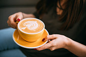 Lady's hands holding cup with latte art