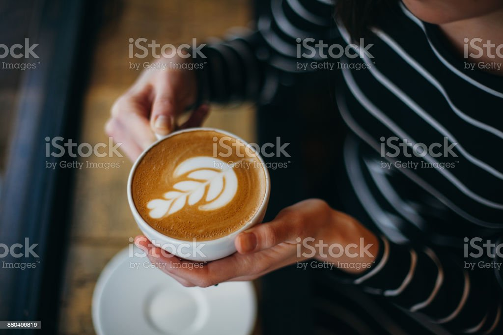 Lady's hands holding cup with sth heart-shaped stock photo