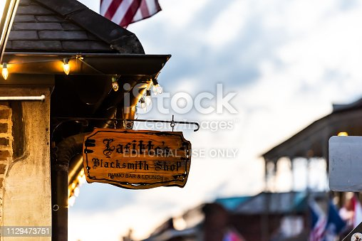 889246424istockphoto Lafitte's blacksmith shop bar sign closeup in French Quarter Louisiana with illuminated lights in evening night 1129473751