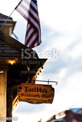 889246424istockphoto Lafitte's blacksmith shop bar sign vertical closeup in French Quarter Louisiana with illuminated lights in evening night 1129473726