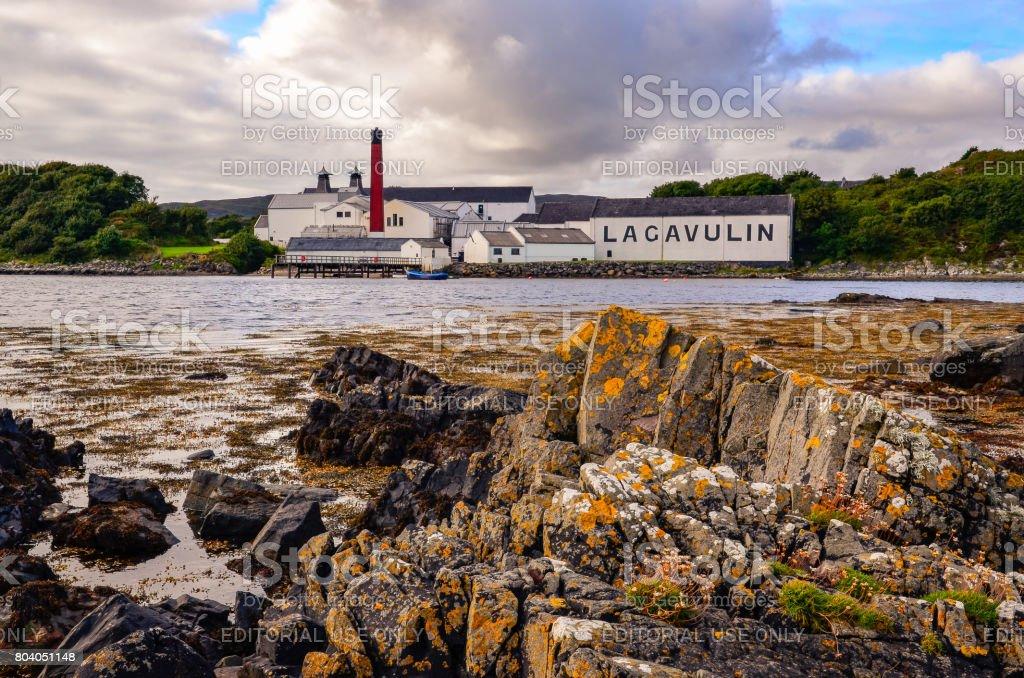 Lagavulin distillery factory with ocean coastline foreground, Islay, United Kingdom stock photo