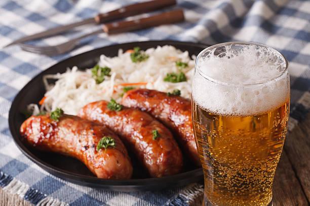lager beer and snacks of sausages and sauerkraut - bratwurst mit sauerkraut stock-fotos und bilder