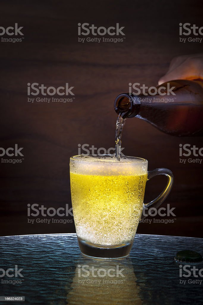 lager beer drain from bottle to glass on table royalty-free stock photo
