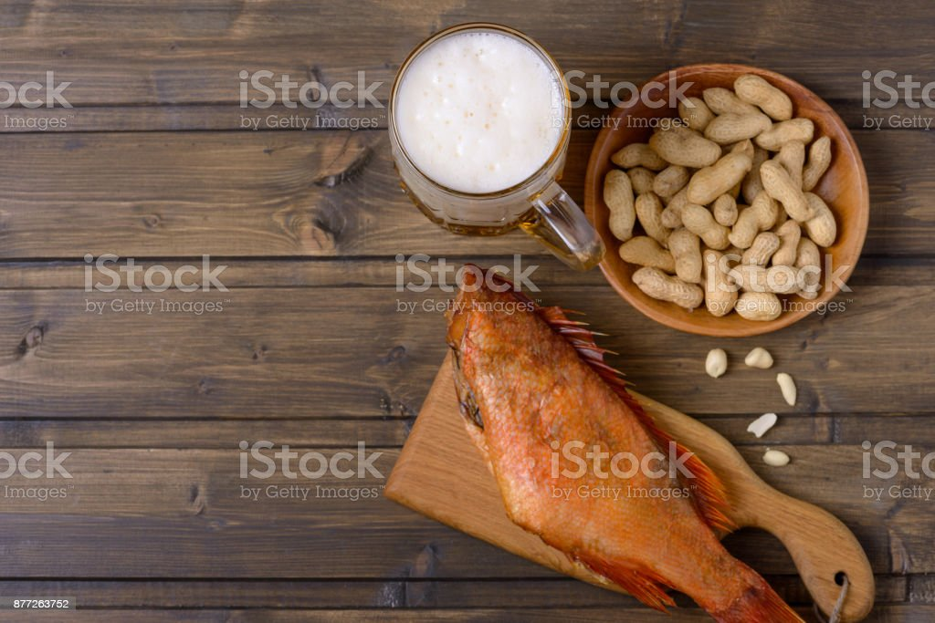 Lager beer mug and fish with peanut. Free space for text stock photo