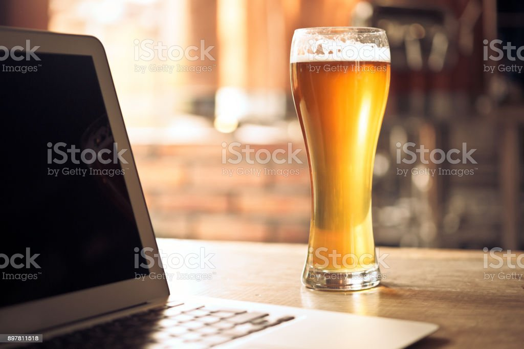 Lager beer with laptop on table at micro brewery Close up of lager beer pint glass with laptop on table at micro brewery Alcohol - Drink Stock Photo