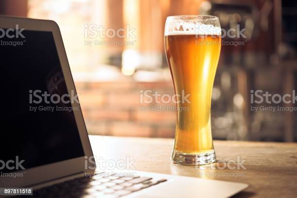 Lager Beer With Laptop On Table At Micro Brewery Stock Photo - Download Image Now