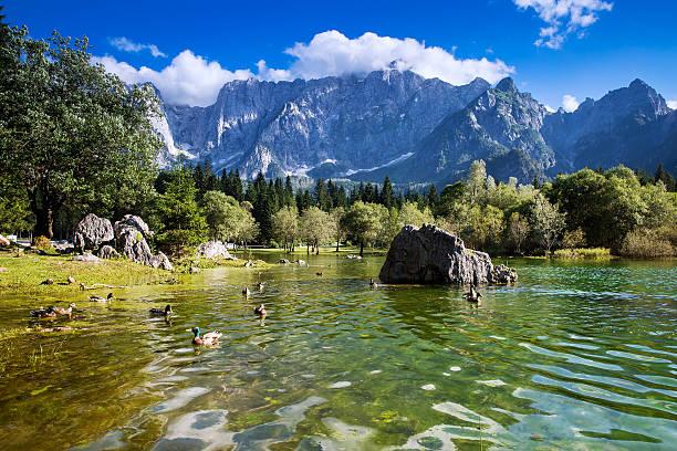 lago di fusine lake with mangart mountains in the background. - friaul julisch venetien stock-fotos und bilder