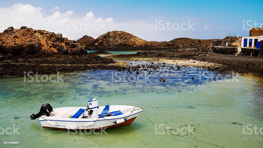 Lagoon with white boat on island Lobos, Fuerteventura. stock photo