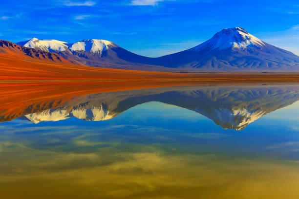 樂–戲劇性的樂湖鏡面反射在金色的日出黎明, 白雪皚皚摩羅火山和火山, 田園詩般的阿卡瑪拉沙漠, 火山景觀全景–聖佩德羅阿卡瑪卡, 智利, bolívia 和阿根廷邊境 - 阿爾蒂普拉諾山脈 個照片及圖片檔