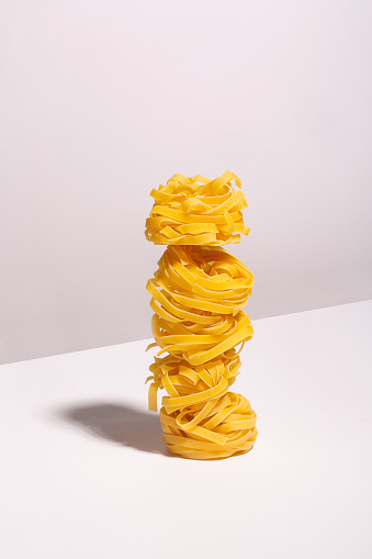 Uncooked spaghetti nests laid out on top of each other with a shadow on a light background. Ingredients for the recipe