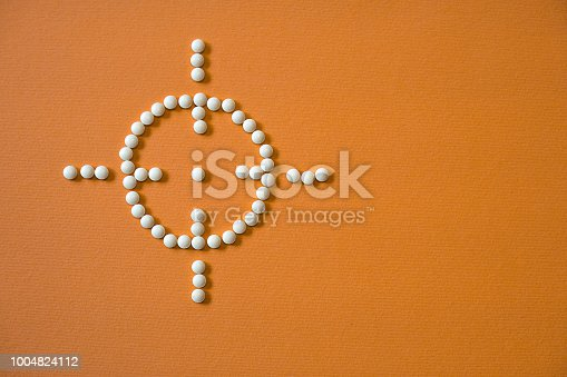 istock laid out sight and a target with pills and medications. The theme of health and saving lives. Stock Photo 1004824112