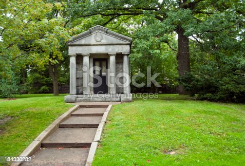 A mausoleum in an urban setting surrounded by green grass and large deciduous trees in the summer months.