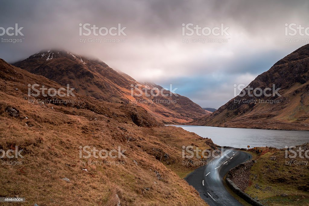 lake and cloud covered mountains stock photo